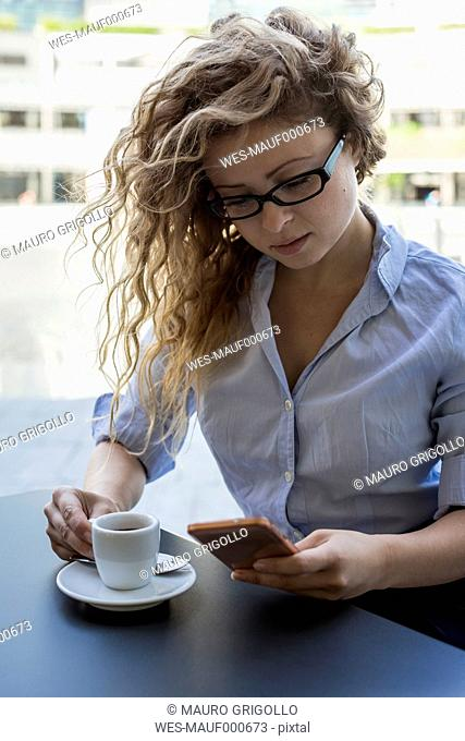 Businesswoman checking cell phone at outdoor cafe