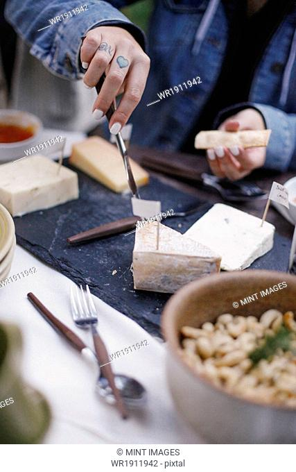 A woman using a knife to cut cheese on a slate board