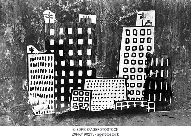 street art collage showing skyscrapers and smaller buildings at night, paris, ile de france, france