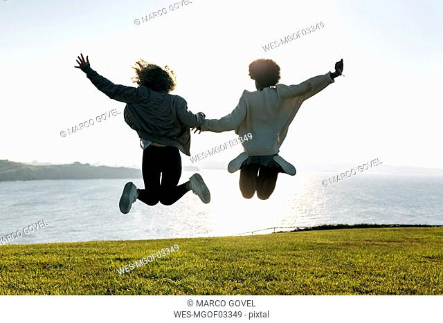 Two best friends jumping at the coast