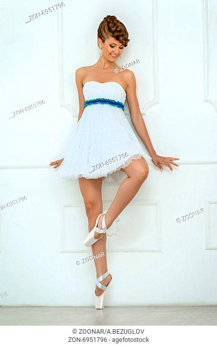 Studio portrait of a ballerina near white wall. Model is wearing a white dress with bare shoulders and stylish hairstyle with braided hair
