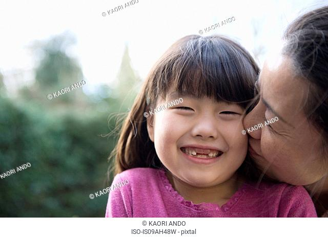 Girl being kissed on the cheek by her mother in the garden