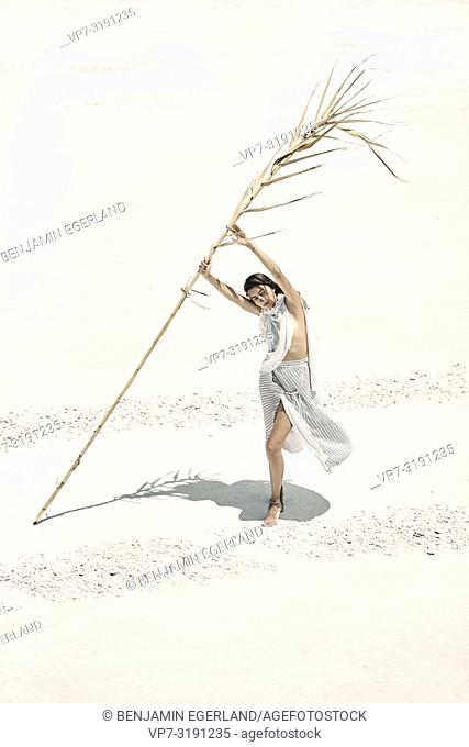 Woman with dry bamboo stick in desert