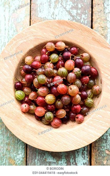 Organic berries. Ripe pink gooseberries in oak plate on shabby blue wooden background copyspace top view