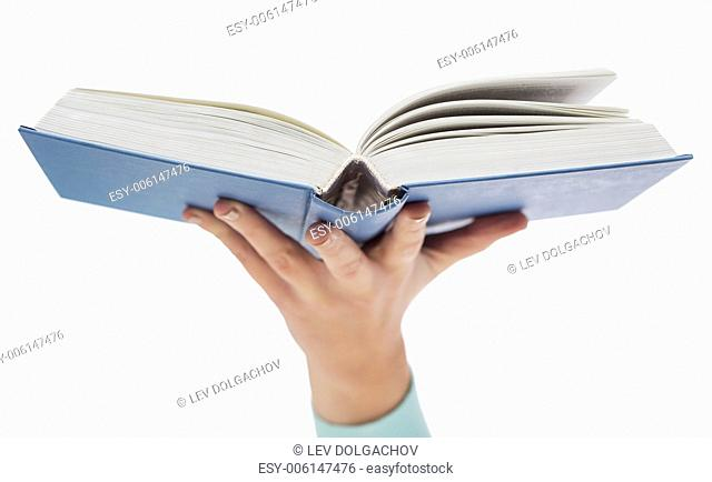 education and book concept - close up of woman hand holding open blue book