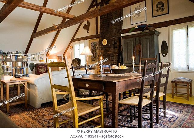 Antique table, chairs and furnishings in the upstairs dining room of an Old Canadiana (circa 1810) Cottage style residential home, Quebec, Canada