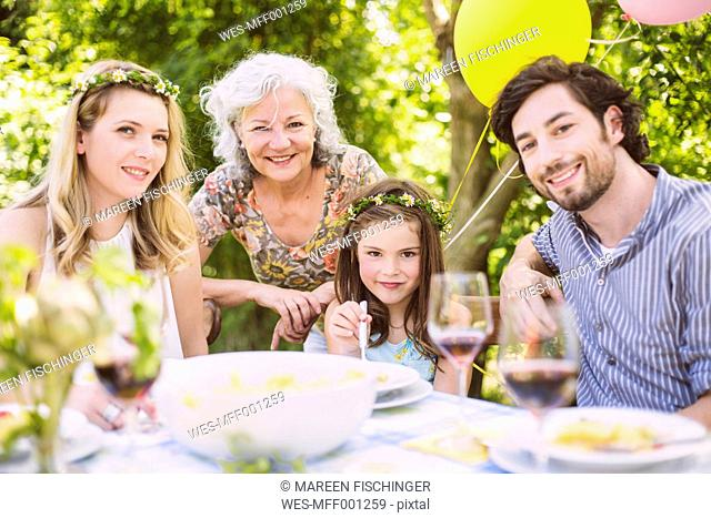 Portrait of happy family of three generations on a garden party