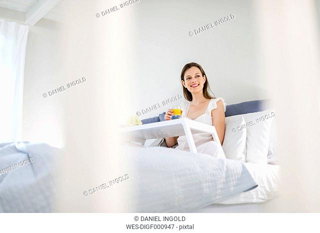 Woman sitting in bed with breakfast tray