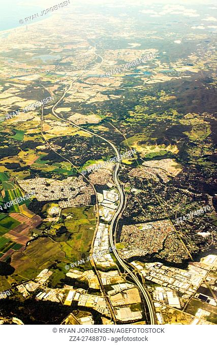 Aerial landscape photo of a major highway running through hinterland and suburbs in the Gold Coast, Queensland, Australia