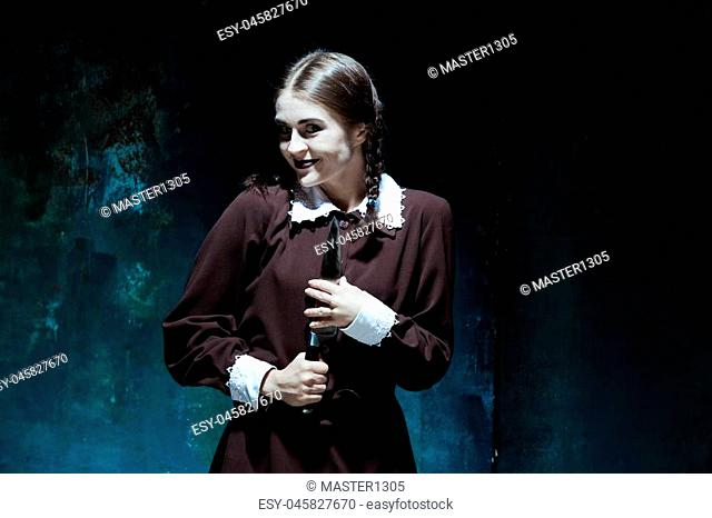 Portrait of a young girl with knife in school uniform as killer woman against school board