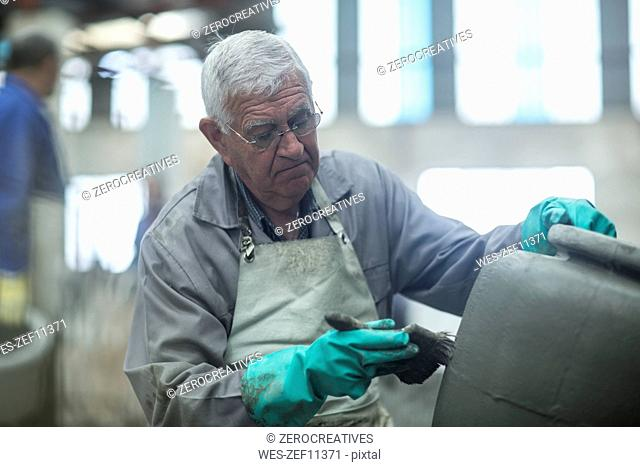 Man working on clay jug in industrial pot factory