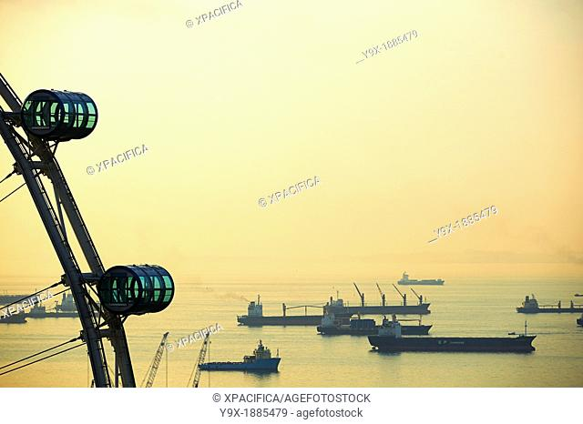 Shipping boats and freighters at sunset off the coast of Singapore as seen through the Singapore Flyer