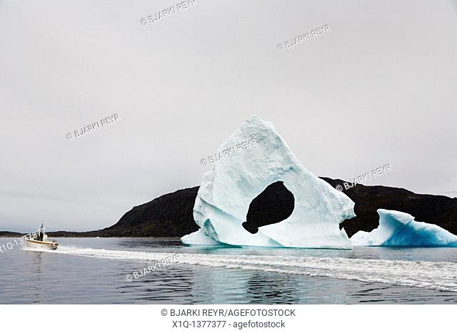 Arched iceberg, boat sailing past, South Greenland