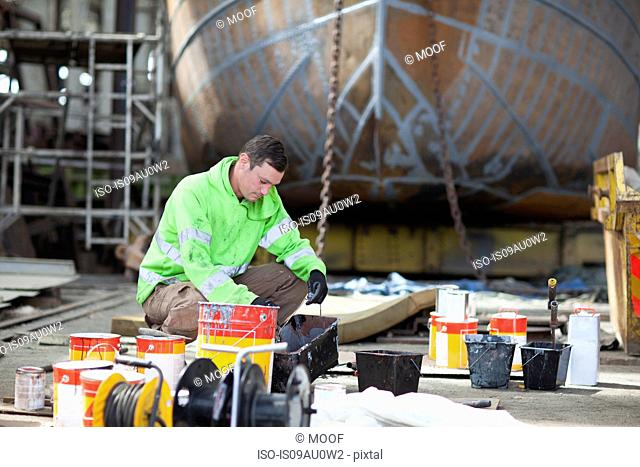 Worker mixing boat paints in shipyard