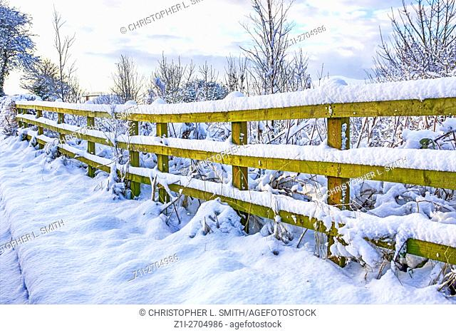 A snow covered ranch fence