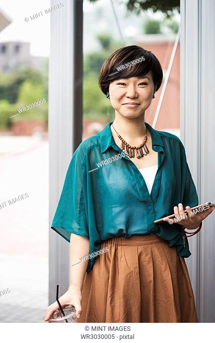Woman with black hair wearing green shirt standing outdoors, holding digital tablet, smiling at camera