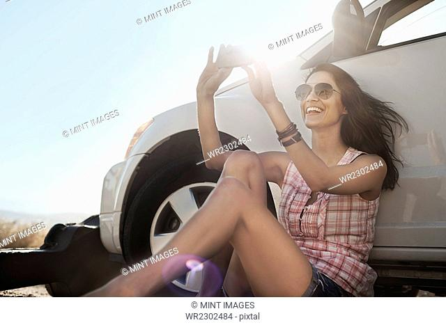 A woman seated in the shade of a car on the road, taking a photograph