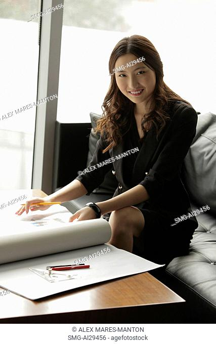Young woman working on plans in an office