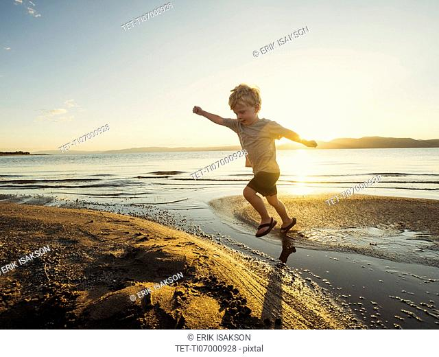 Small boy (4-5) jumping over water on sunny day