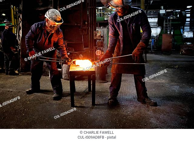 Forge worker hands over pre formed steel billet to colleague for presentation to set of two dies in hammer to be fully forged into crank shaft