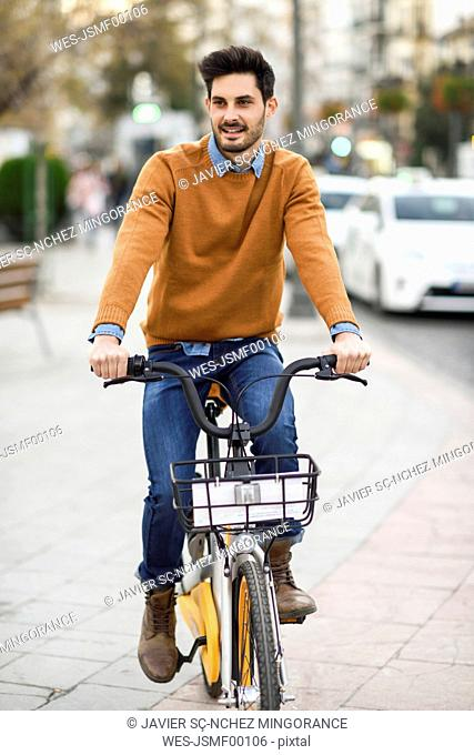 Portrait of young man riding rental bike in the city