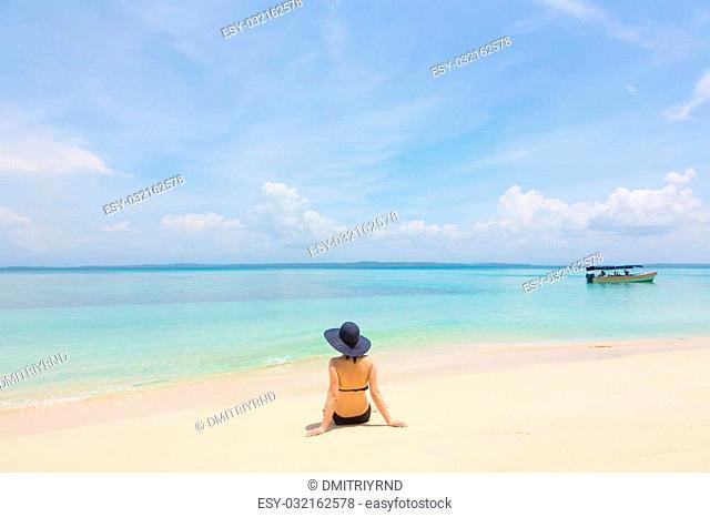 Woman sitting on the beach, archipelago Bocas del Toro, Panama