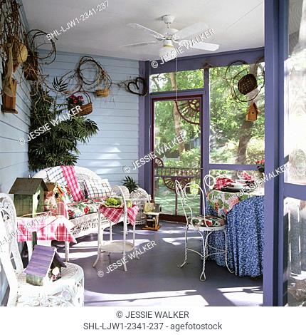 PORCH - Corner of screened porch with wicker couch. Birdhouses. Gray walls, soda fountain chairs, skirted table, grapvine tacked up on walls, ceiling fan