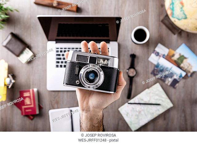 Overhead view of man's hand holding camera and travel items on table