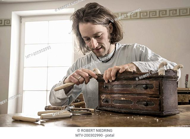 Carpenter carving on an antique bone box at workshop, Bavaria, Germany