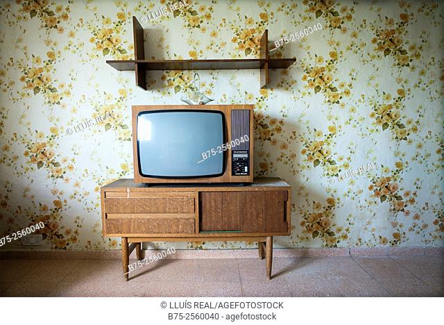 Vintage living room with a floral wallpaper in the wall, and a vintage TV on top of a cabinet. Maó, Mahon, Menorca, Biosphere Reserve, Balearic Islands, Spain