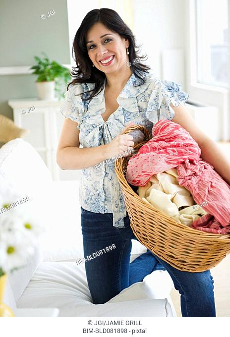 Smiling Hispanic woman carrying basket of laundry