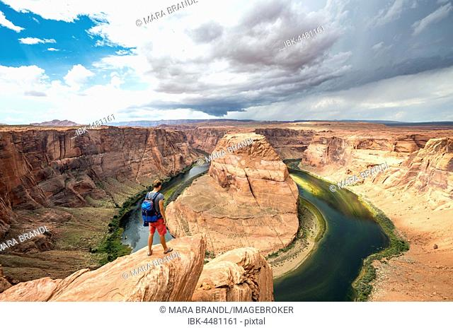 Young man on a rock, Horseshoe Bend, bend of the Colorado River, King Bend, Glen Canyon National Recreation Area, Page, Arizona, USA