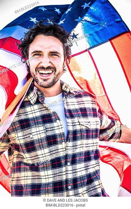 Smiling Hispanic man holding American flag