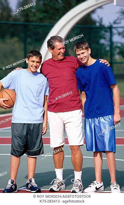 dad and his two sons on the basketball court