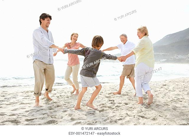 Portrait of a cute family playing on the beach over bright background