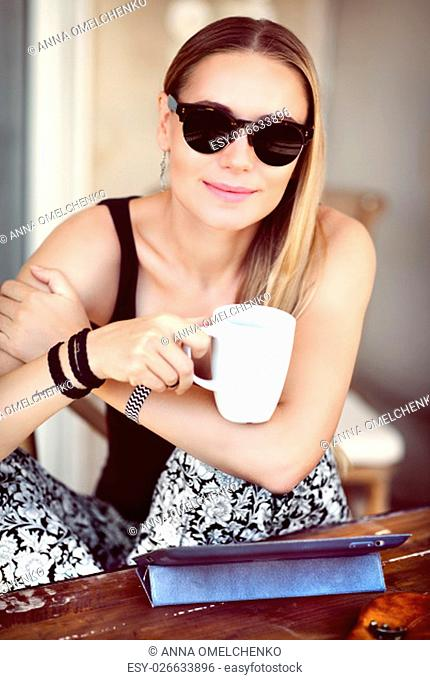 Portrait of a stylish girl having breakfast outdoors, with pleasure drinking coffee in the cafe, enjoying peaceful morning