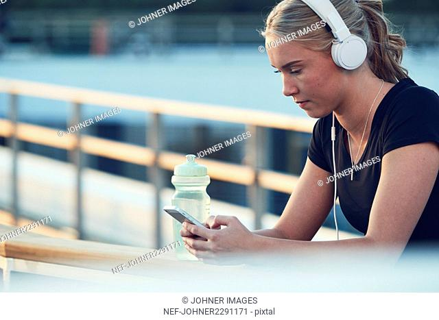 Woman with headphones using cell phone