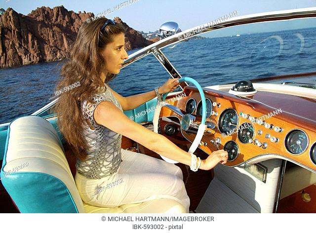 Young woman at the wheel of a Riva Motorboat, Théoule-sur-Mer, France, Europe