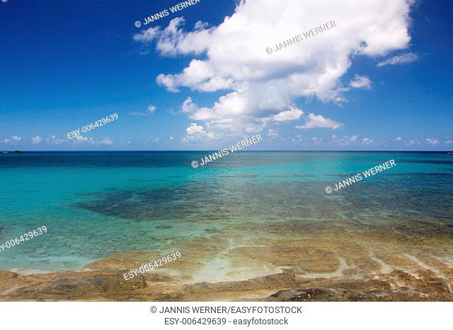 Shallow water leads from a rocky beach into the vast Caribbean Sea in the Bahamas