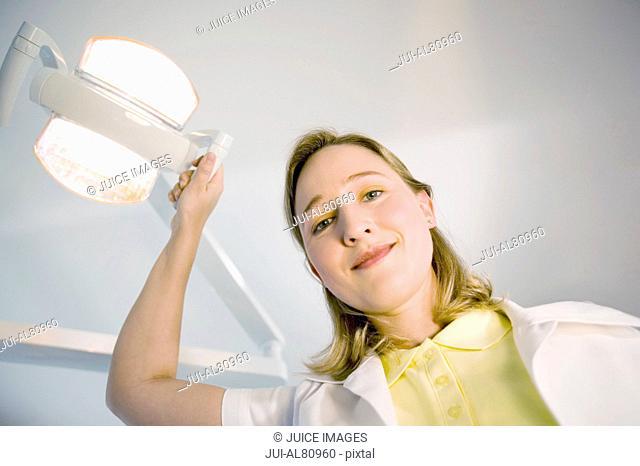 Female dental assistant smiling and adjusting dental light