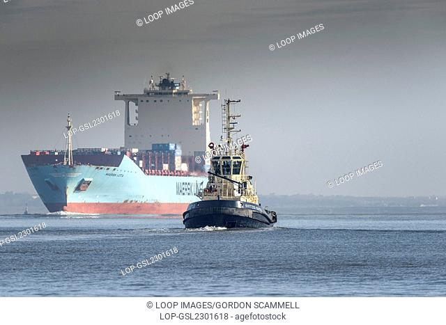 The tug Switzer Bootle escorts the container ship Maersk Lota as she steams upriver on the River Thames