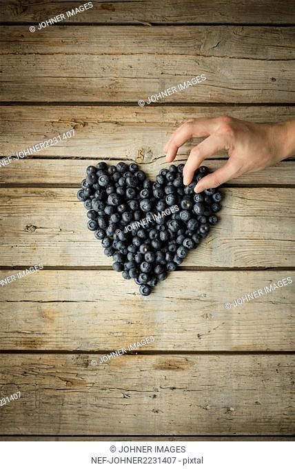 Hand making heart out of blueberries