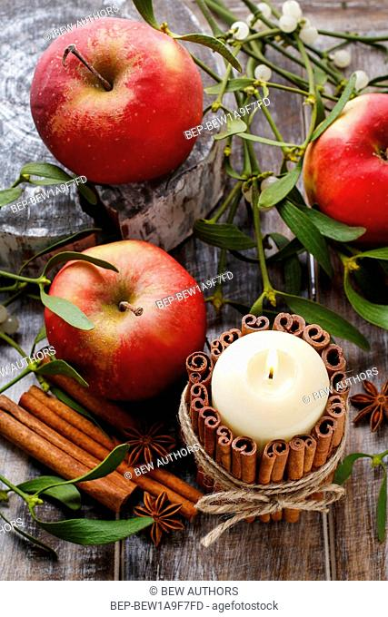 Candle decorated with cinnamon sticks, apples and mistletoe in the background