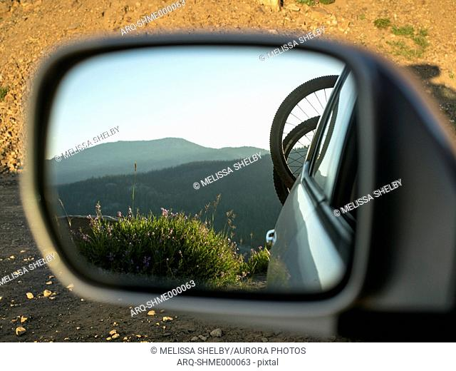 Photograph with mountain bicycles on rack on back of car reflecting in side view mirror, McCall, Idaho, USA