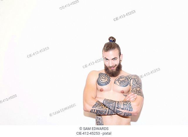 Portrait confident male hipster with bare chest and tattoos