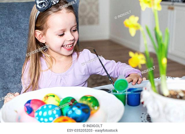 Smiling little girl coloring easter eggs. Cozy home atmosphere. Easter