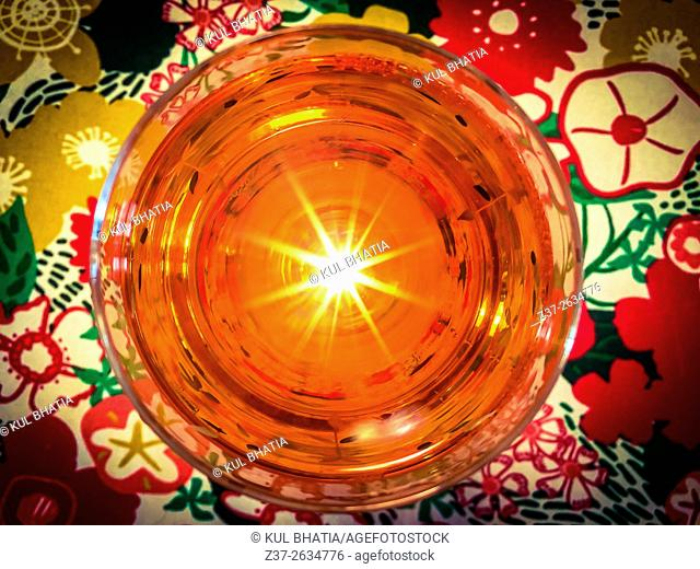 Cheerful drink. An overhead light is reflected in the glass as a flare, Ontario, Canada