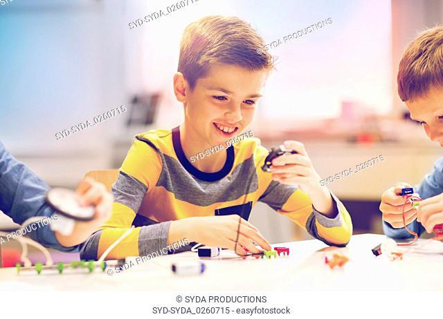 happy boy building robot at robotics school