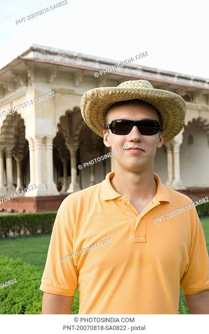 Young man standing in front of a mausoleum, Taj Mahal, Agra, Uttar Pradesh, India