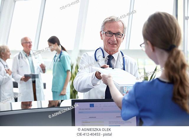 Male doctor handing clipboard to female nurse at hospital nurses station